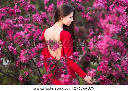 Beautiful young woman in elegant red dress posing among pink trees in garden - stock photo