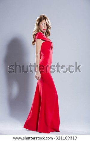 Beautiful young woman in elegant red night dress - stock photo