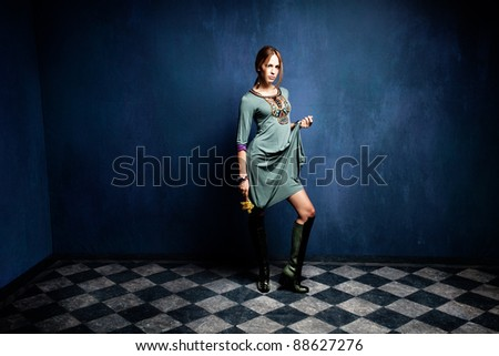 beautiful young woman in empty room standing holding flower in one hand - stock photo