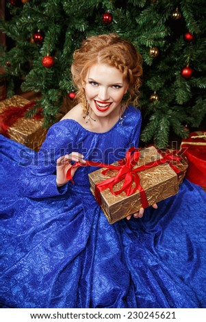 Beautiful young woman in evening dress holding present over Christmas background. - stock photo