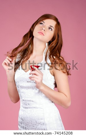 Beautiful young woman in evening gown with cocktail in hand - stock photo