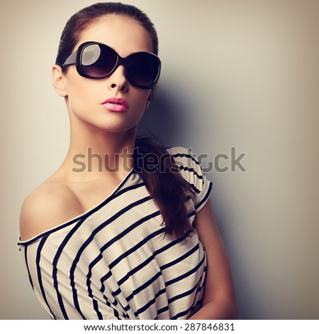 Beautiful young woman in fashion sunglasses posing and looking. Vintage closeup portrait - stock photo