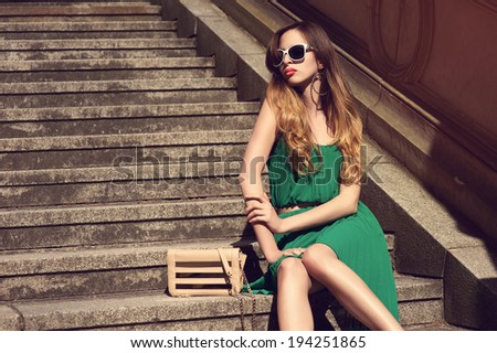 beautiful young woman in fashionable green dress on stairs - stock photo
