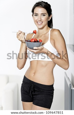 beautiful young woman in fitness clothes eating fresh fruit from a bowl at home - stock photo