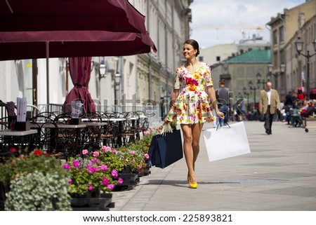 Beautiful young woman in flowers dress, against of summer street - stock photo
