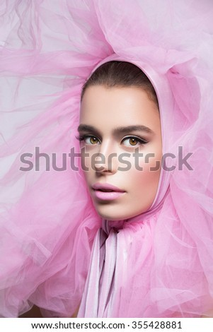 Beautiful young woman in fluffy pink headwear. Close up. Beauty shot. Over grey background. - stock photo