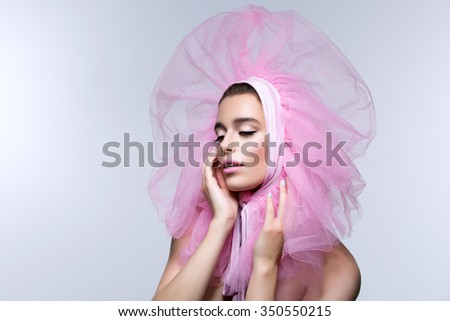Beautiful young woman in fluffy pink headwear looking to the side. Close up. Beauty shot. Over grey background. Copy space. - stock photo