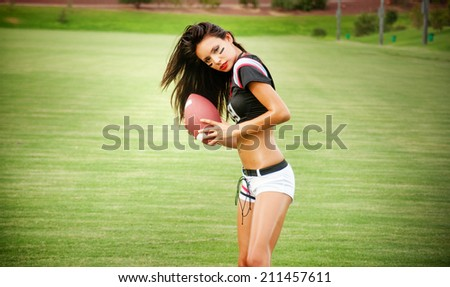 Beautiful young woman in football top and shorts holding ball ( American ) - stock photo
