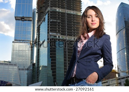 Beautiful young woman in front of modern office buildings - stock photo