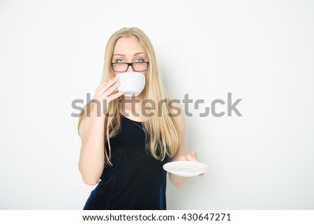Beautiful young woman in glasses wearing dark-blue dress drinking coffee, with copyspace (on light background)