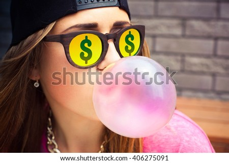 Beautiful young woman in glasses with dollars blowing a bubble gum balloon  - stock photo