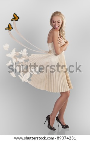beautiful young woman in golden dress with butterfly all around playing with her elegant skirt - stock photo