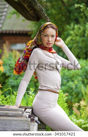 Beautiful young woman in gray dress in summer park - stock photo