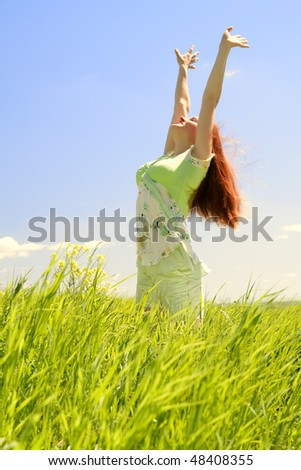Beautiful young woman in green field at blue sky background - stock photo