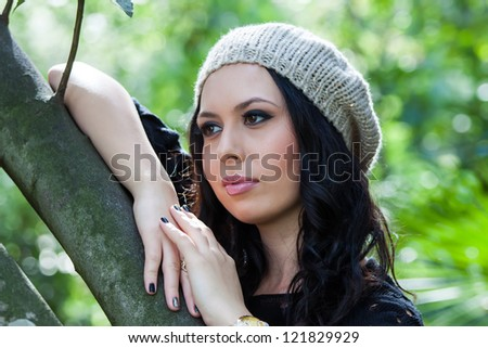 beautiful young woman in hat posing in the park
