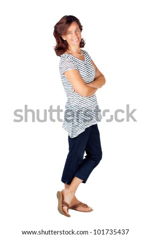 Beautiful young woman in her 30s standing with her hands folded against white background and wearing top with stripes and jeans