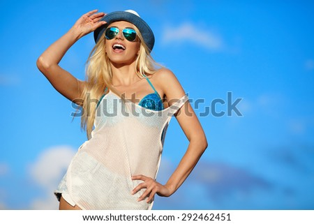 Beautiful young woman in hipster  hat and sunglasses posing over sky. - stock photo