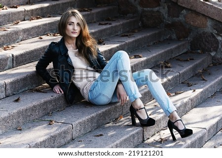 Beautiful young woman in jeans sitting on the stairs, outdoor - stock photo