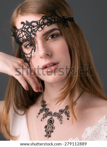 Beautiful Young Woman in Lace Mask - stock photo