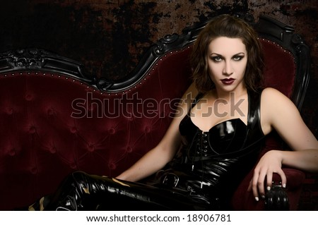 Beautiful young woman in latex catsuit on classic red couch - stock photo
