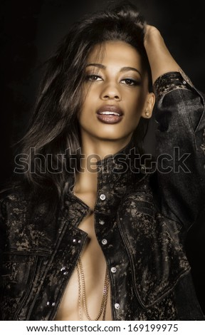 Beautiful young woman in leather jacket - stock photo