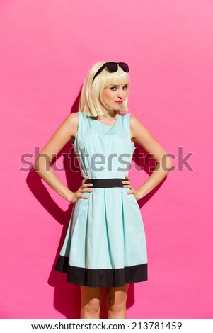 Beautiful young woman in light blue dress posing with hands on hip. Three quarter length studio shot on pink background. - stock photo