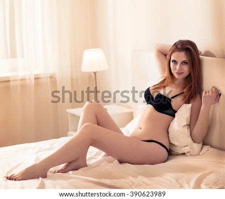 Beautiful young woman in lingerie on the bed - stock photo
