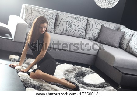 Beautiful young woman in living room on sofa .Fashion light and colors.