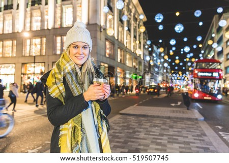 Beautiful young woman in London in winter. She is blonde, in her early twenties, holding a cup of coffee and wearing warm clothes. Christmas lights and traffic in background.