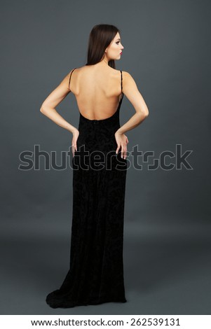 Beautiful young woman in long black dress on dark gray background - stock photo