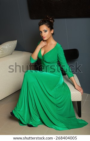 Beautiful young woman in long green evening dress sitting on chaIr - stock photo