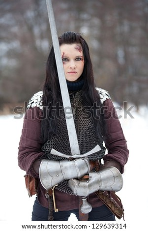 Beautiful young woman in medieval clothes holding a sword