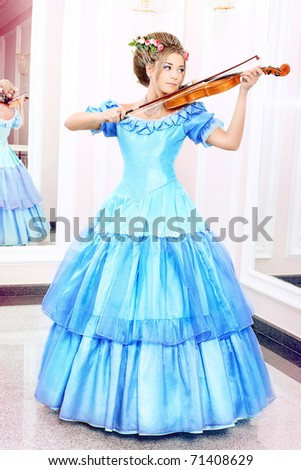 Beautiful young woman in medieval era dress playing the violin. - stock photo