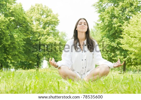 Beautiful young woman in meditation pose outdoors. - stock photo
