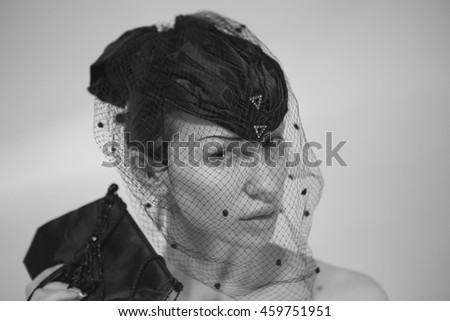 Beautiful young Woman in Mourning. Black and White, soft focus. Sad Emotional Calm Woman face. Female elegant Portrait in the classic black Mourning Hat with a veil. Sorrow and grief