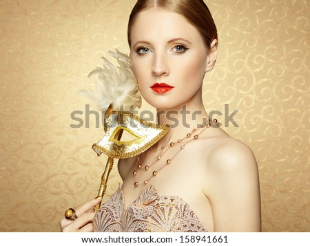 Beautiful young woman in mysterious golden Venetian mask. Fashion photo - stock photo