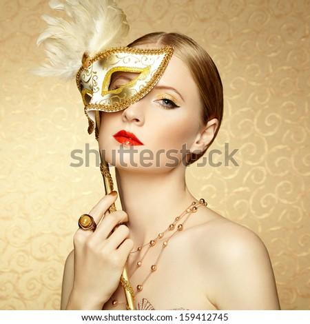Beautiful young woman in mysterious golden Venetian mask. Fashion photo - stock photo