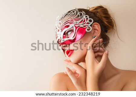 Beautiful young woman in mysterious venetian carnival mask. Fashion photo - stock photo