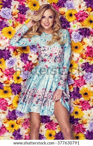 Beautiful young woman in nice blue dress posing on colorful wall of flowers. Fashion photo, nice hair, big smile - stock photo