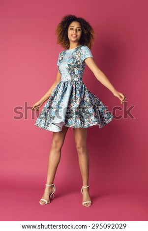 Beautiful young woman in nice flower pattern dress and high heels sandals. Fashion Photo. Afro hairstyle