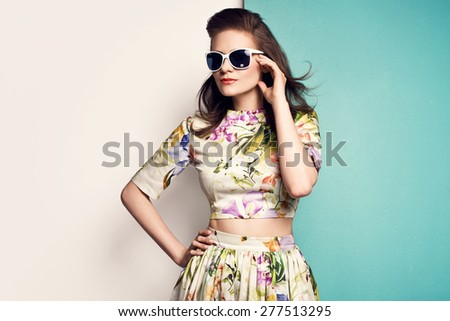 beautiful young woman in nice spring dress  with flower pattern, sunglasses, posing on yellow background in studio. Fashion photo - stock photo