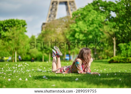 Beautiful young woman in Paris lying on the grass near the Eiffel tower on a nice spring or summer day  - stock photo