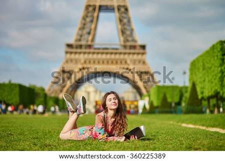 Beautiful young woman in Paris lying on the grass near the Eiffel tower on a nice spring or summer day and reading a book. Student or schoolgirl doing her homework or preparing to exams - stock photo