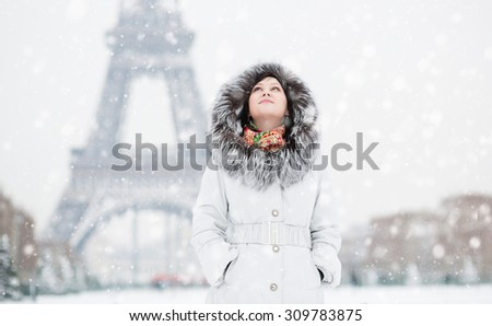 Beautiful young woman in Paris near the Eiffel tower, enjoying beautiful winter day and snow falling from the sky. Rare snowy day in Paris