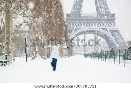 Beautiful young woman in Paris near the Eiffel tower, enjoying beautiful winter day and snow falling from the sky. Rare snowy day in Paris, girl is jumping happily - stock photo
