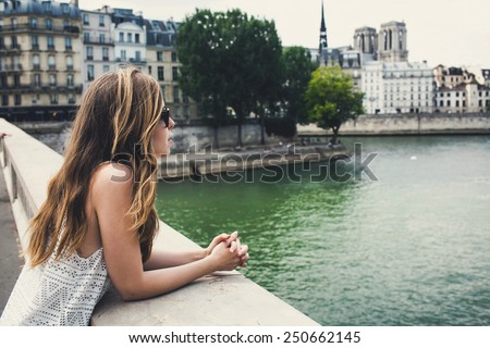Beautiful young woman in Paris on holidays in France staying near Seine river while walking on Champs-Elysees, Paris, France - stock photo