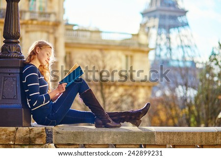 Beautiful young woman in Paris, reading a book  - stock photo