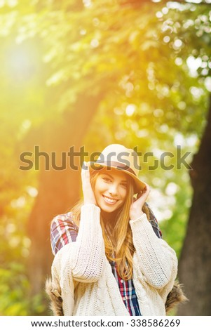 Beautiful young woman in park in autumn. Gorgeous teenage girl in beige hat and sweater outdoors in fall smiling and posing. Vertical, retouched, vibrant colors.