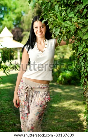 beautiful young woman in park, posing near tree