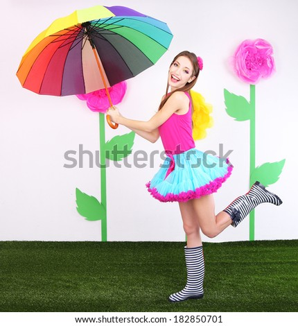 Beautiful young woman in petty skirt with umbrella on decorative background - stock photo
